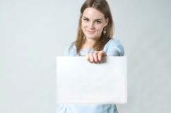 Young woman showing blank piece of paper Stock Image