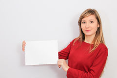 Young Woman showing a blank sheet of paper Stock Images