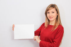 Young Woman showing a blank sheet of paper Royalty Free Stock Photography