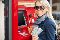 Young woman showing cash after withdrawal from ATM Stock Image
