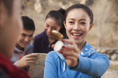 Young woman showing compass to her friend Stock Photos