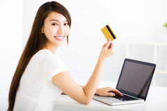 Young woman showing credit card and laptop. Happy young woman showing credit card and laptop royalty free stock photography