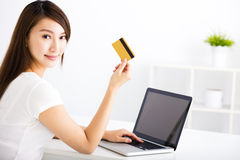 Young woman showing credit card and laptop Stock Images