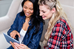 Young woman showing digital tablet to female friend Royalty Free Stock Photos