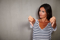 Young woman showing disapproval sign at camera. Young woman of caucasian ethnicity showing disapproval sign at camera Royalty Free Stock Photography