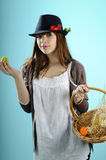 Young woman showing easter basket. Teenager girl with black hat showing egg from easter basket Royalty Free Stock Photography