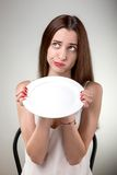 Young woman showing empty plate. Woman with plate in studio on white background Stock Images