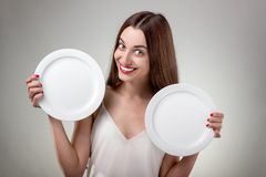 Young woman showing empty plates. Royalty Free Stock Photos