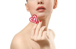 Young woman showing heart shaped candy. Stock Photo