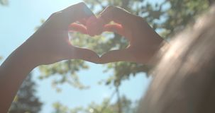 Female hands in shape of heart over green nature and blue sky. Young woman showing heart symbol over blue sky stock images