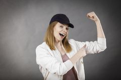Young woman showing her arm muscles. Young sporty woman wearing cap and sportswear showing her arm muscles enjoying workout results. Studio shot on grey stock photo