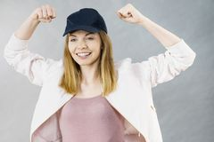 Young woman showing her arm muscles. Young sporty woman wearing cap and sportswear showing her arm muscles enjoying workout results. Studio shot on grey stock photos