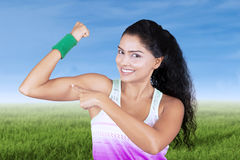 Young woman showing her bicep in meadow Royalty Free Stock Photos