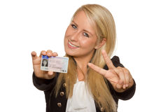 Young woman showing her driver's license. 16 to 18 year old girl just received her driver license Royalty Free Stock Photos