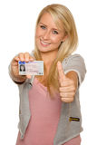 Young woman showing her driver's license. 16 to 18 year old girl just received her driver license Stock Images