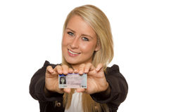 Young woman showing her driver's license. 16 to 18 year old girl just received her driver license Royalty Free Stock Images