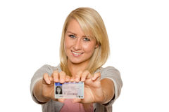 Young woman showing her driver's license. 16 to 18 year old girl just received her driver license Royalty Free Stock Photography