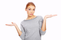Young woman showing her ignorance. Shrugging her shoulders and holding her hands in the air while looking at the camera with a raised eyebrow Royalty Free Stock Image