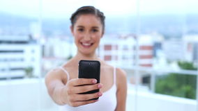 Young woman showing her mobile phone and texting a message Stock Images