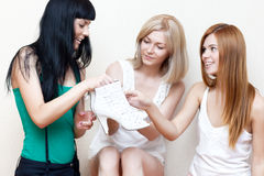 Young woman showing her new shoes to friends Stock Photography