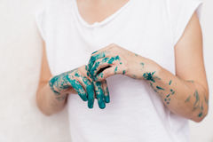 Young woman showing her painted hands. With blue green color in front of white background royalty free stock photo