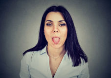 Young woman showing her tongue teasing you. Portrait of a young woman showing her tongue royalty free stock photo