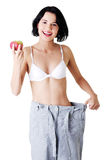 Young woman showing how much weight did she lost. Royalty Free Stock Photography