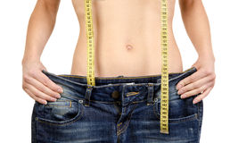 Young woman showing how much weight she lost. Stock Image