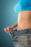Young woman showing how much weight she lost. Royalty Free Stock Image