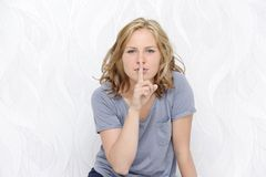 Young woman showing a hush sign Stock Photography