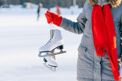 Young woman showing ice skates for winter. Ice skating sport activity in white hat smiling isolated on a white background Stock Photography