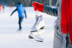 Young woman showing ice skates for winter. Ice skating sport activity in white hat smiling isolated on a white background Royalty Free Stock Photography