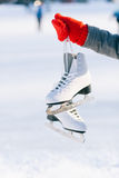 Young woman showing ice skates for winter. Ice skating sport activity in white hat smiling isolated on a white background Stock Photos