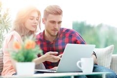 Young woman showing important information to her boyfriend on the laptop screen Royalty Free Stock Image