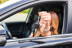 Young woman showing key in a car Stock Images