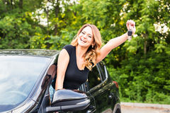 Young woman showing key in a car Royalty Free Stock Photo