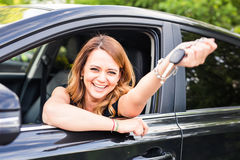 Young woman showing key in a car Stock Photo