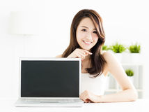 Young woman showing laptop screen. Smiling young woman showing laptop screen Royalty Free Stock Photography