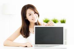 Young woman showing laptop screen. Smiling young woman showing laptop screen stock image