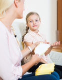 Young woman showing little daughter sanitary napking at home Royalty Free Stock Images