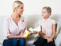 Young woman showing little daughter sanitary napking at home Stock Image