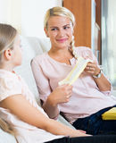 Young woman showing little daughter sanitary napking at home Stock Photos