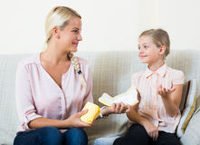 Young woman showing little daughter sanitary napking at home. Confidential conversation between mother and daughter about menstruation Stock Photography