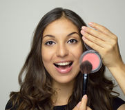 Young woman showing make-up cosmetic products. Beautiful smiling girl with wavy hair presenting makeup stock images