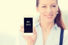 Young woman showing mobile smart phone with big sale sign on screen. Smiling female holding mobile smart phone with big sale sign on screen, isolated outside Royalty Free Stock Photography
