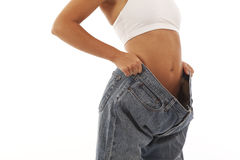 Young woman showing off weight loss. With jeans Royalty Free Stock Image