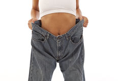 Young woman showing off weight loss. With jeans Royalty Free Stock Photography