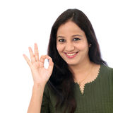 Young woman showing OK sign against white background Stock Images