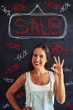 Young woman showing ok sign posing against sale advertisement Royalty Free Stock Photo