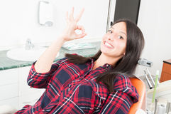 Young woman showing okay gesture on dentist chair Stock Photos